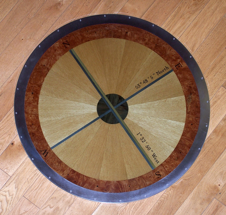 Compass Tablet installed with protective plate-glass and metal ring securing it to museum floor. The blue metal (latitude) is bright steel and green (longitude) is brass. The plate-glass distorts the colours.