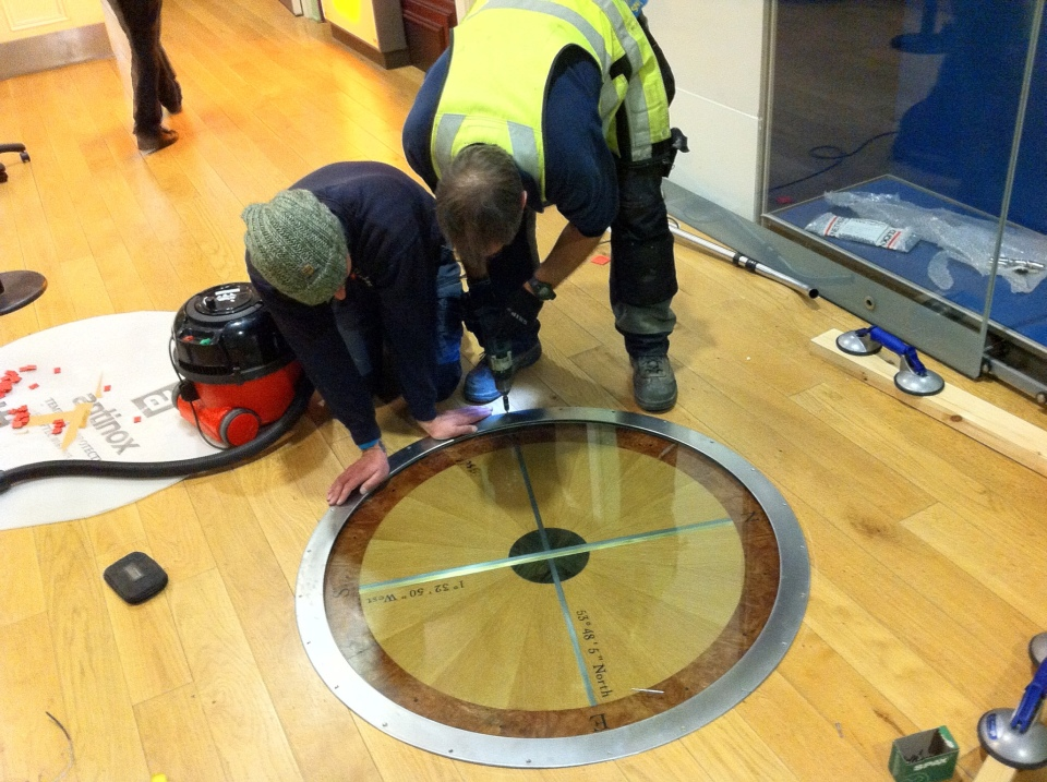 Compass inserted into the museum floor. A one inch thick plate glass protecting the work, and a large steel band holding it all in place.